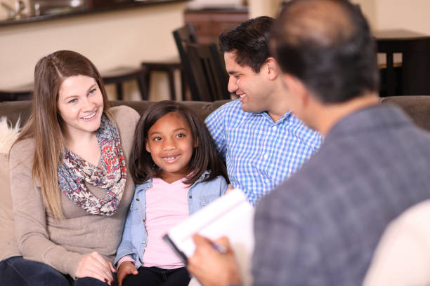 Family counseling session at home with therapist. Multi-ethnic family at home with mental health professional, social worker, or family therapist.  Adopted child with young family. alternative therapy stock pictures, royalty-free photos & images