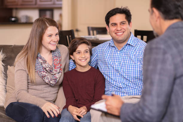 Family counseling session at home with therapist. Multi-ethnic family at home with mental health professional, social worker, or family therapist.  Child with young family. alternative therapy stock pictures, royalty-free photos & images
