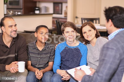 Multi-ethnic family at home with mental health professional, social worker, or family therapist.