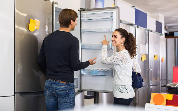 family couple choosing new refrigerator in hypermarket stock photo