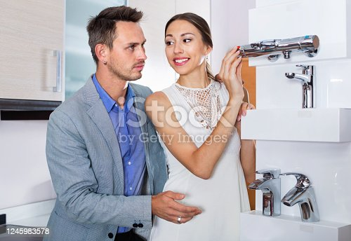 Happy cheerful young family couple looking for modern functional mixer tap in furniture store