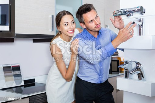 Happy  young family couple looking for modern functional mixer tap in furniture store