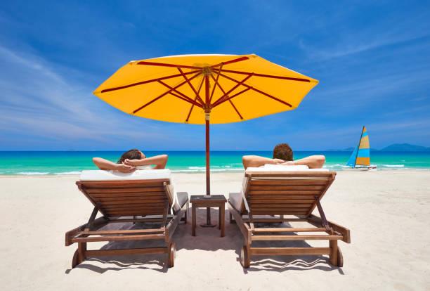 Family couple on tropical beach on deck chairs under orange umbrella stock photo