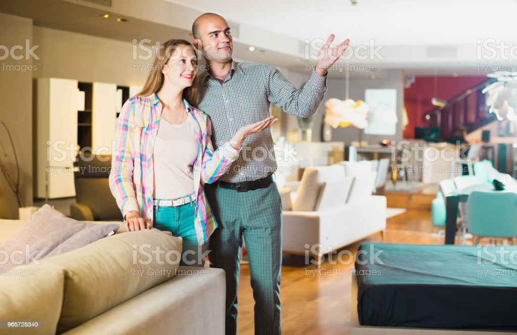 Family couple visiting salon of furniture in search of new couch - Royalty-free Adult Stock Photo