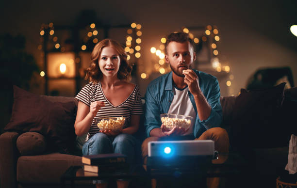 Family couple watching television projector at home on sofa Family couple watching television projector at home on the sofa movie stock pictures, royalty-free photos & images