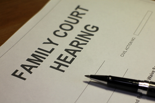 Someone filling out Family Court Hearing document.