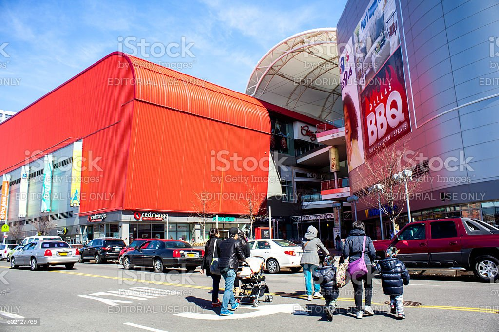 Family crosses street to head into Rego Park shopping center. stock photo