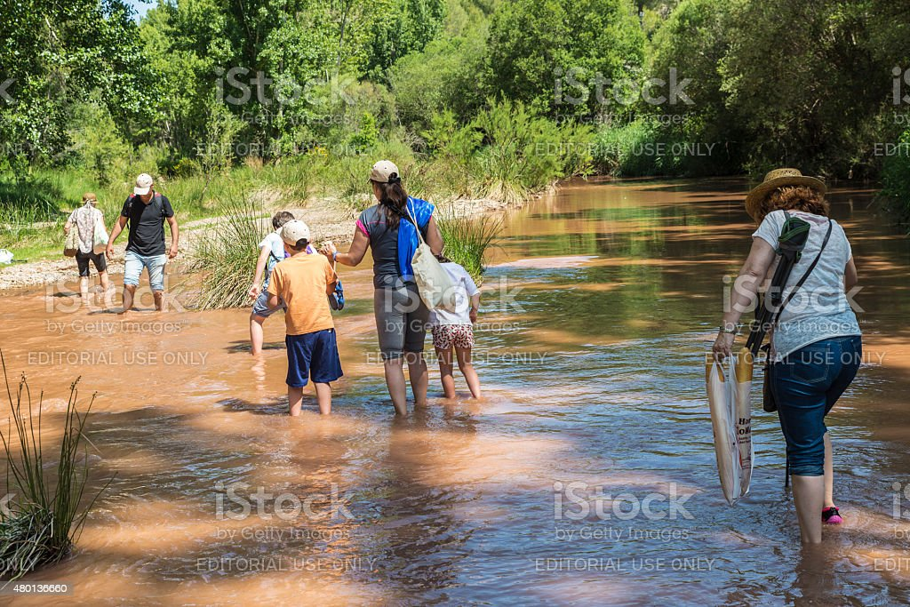 Family crossing a river stock photo