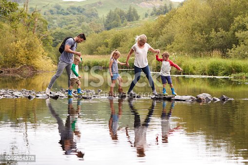 istock Family Crossing River Whilst Hiking In UK Lake District 1049854378