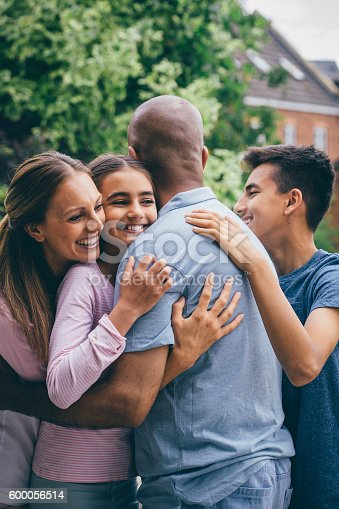 Happy family sharing a cuddle outdoors. Everone is wrapping their arms round the father who has his back to the camera.