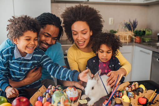 Happy young children petting white rabbit with their parents