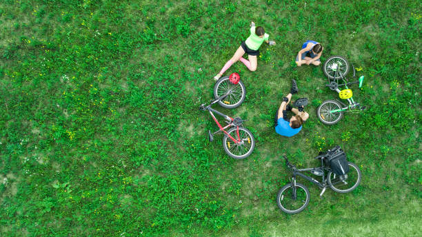 Family cycling on bikes outdoors aerial view from above, happy active parents with child have fun and relax on grass, family sport and fitness on weekend stock photo