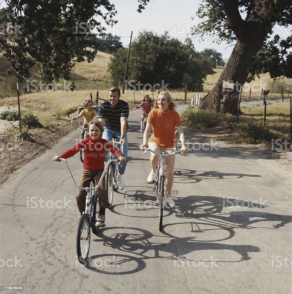 Family cycling on road stock photo