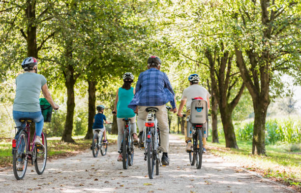 family cycling together through park - cycling stock photos and pictures