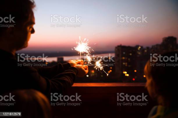 Family dad and two kids with sparklers at sunset on the balcony of picture id1221612579?b=1&k=6&m=1221612579&s=612x612&h=ye jrfzlmj ntcf g33meijbxdqvxvxglalwt9w9acw=