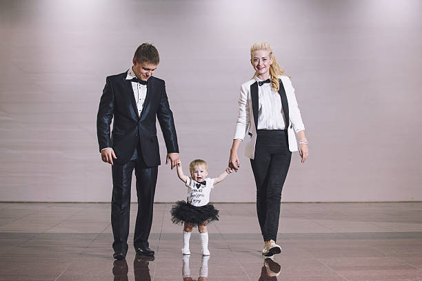 family, dad, mom and daughter stylish and fashionably dressed - festliche babymode junge stock-fotos und bilder
