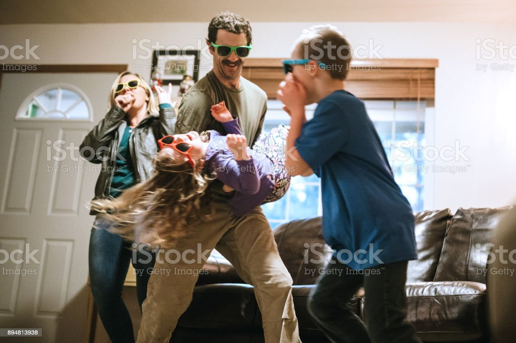 Family Dancing and Singing in Living Room stock photo