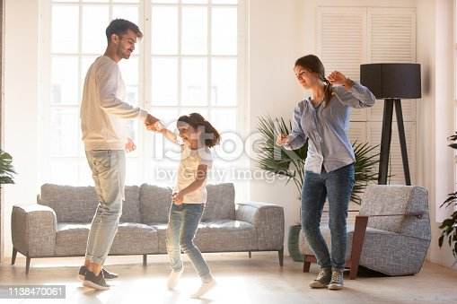 Family mother father and preschool adorable daughter in living room moving dancing to music little girl holding father hand having fun enjoy time with parents at home. Funny leisure activities concept