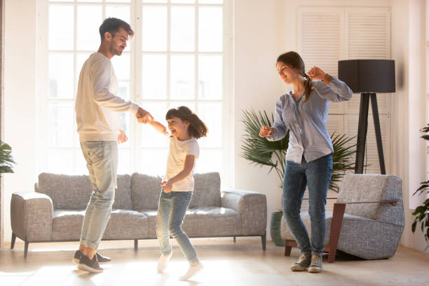 family dancing in living room spending time on weekend together - family home zdjęcia i obrazy z banku zdjęć