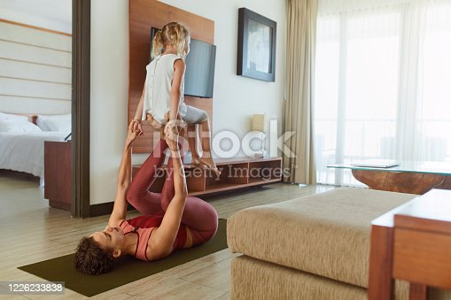 916126642 istock photo Family. Daughter And Mother Practicing Partner Yoga At Home. Young Woman And Child Exercising Together. Sporty Parent And Kid Doing Acroyoga In Living Room. 1226233838