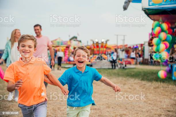 Family visit the fairground to enjoy the rides together. Little boys are running towards the camera. Parents walking behind.