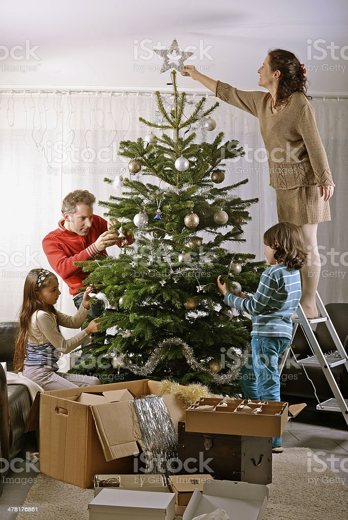 Family decorates Christmas Tree stock photo