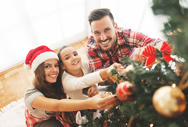 family decorating a christmas tree - christmas families stock photos and pictures