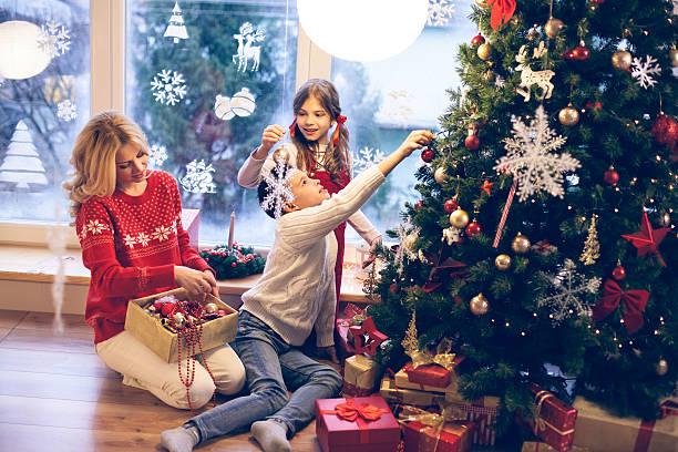 familie dekorieren weihnachtsbaum - weihnachtlich dekorieren stock-fotos und bilder