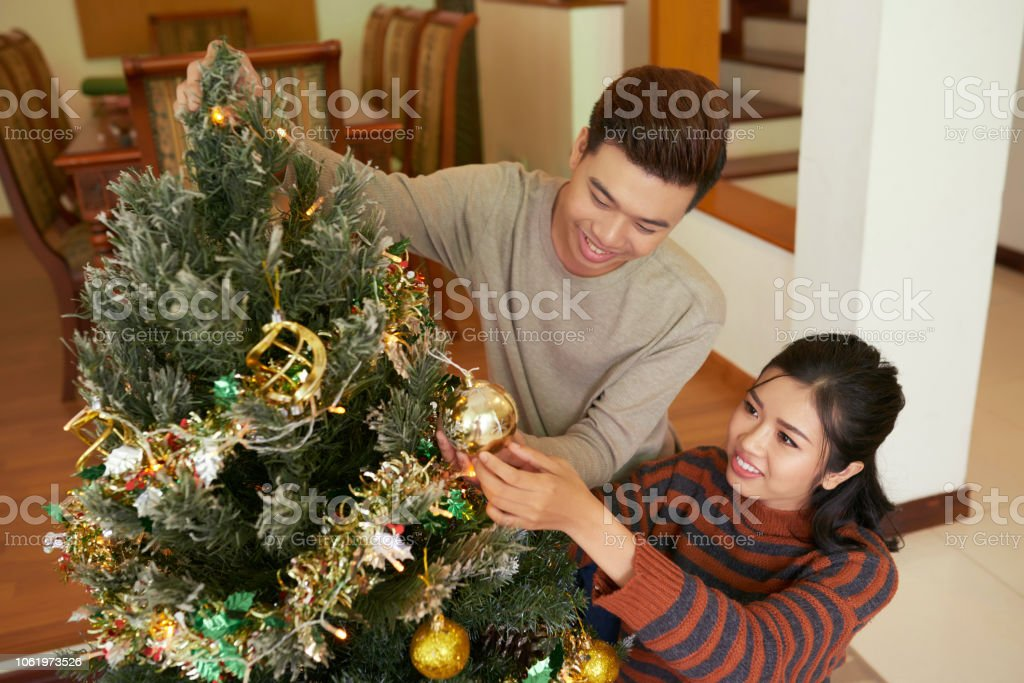 Cheerful family hanging decorations on fir tree for winter holidays