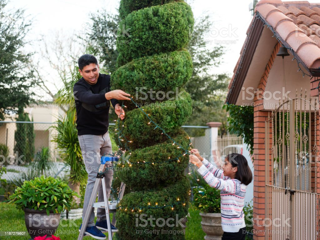 Family Decorating Outdoors Home For Christmas Stock Photo Download Image Now Istock