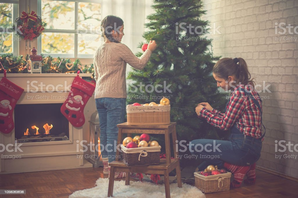Two beautiful sisters decorating the Christmas tree at home