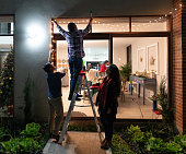 istock Family decorating the house for Christmas and hanging lights 1165432311