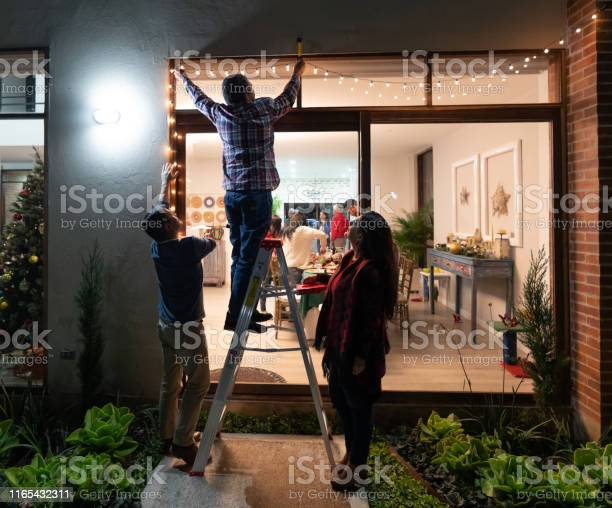 Family decorating the house for christmas and hanging lights picture id1165432311?b=1&k=6&m=1165432311&s=612x612&h=p 4n9lo5wmys6ybkflafcfwwcgarcbl4ze6q3du759y=