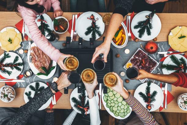dinig de famille à la table en bois avec le gril de raclette - raclette photos et images de collection