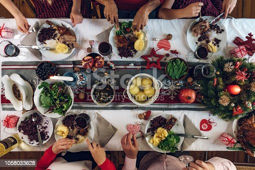 family eating celebrity meal at festive Christmas table