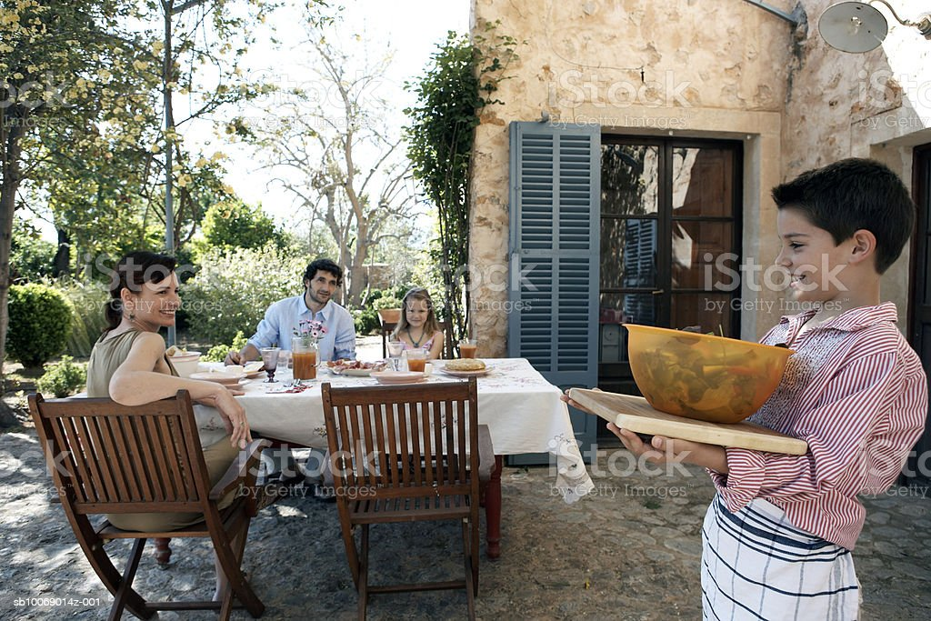 Family dining outdoors, boy (8-9) carrying bowl with salad royalty-free stock photo
