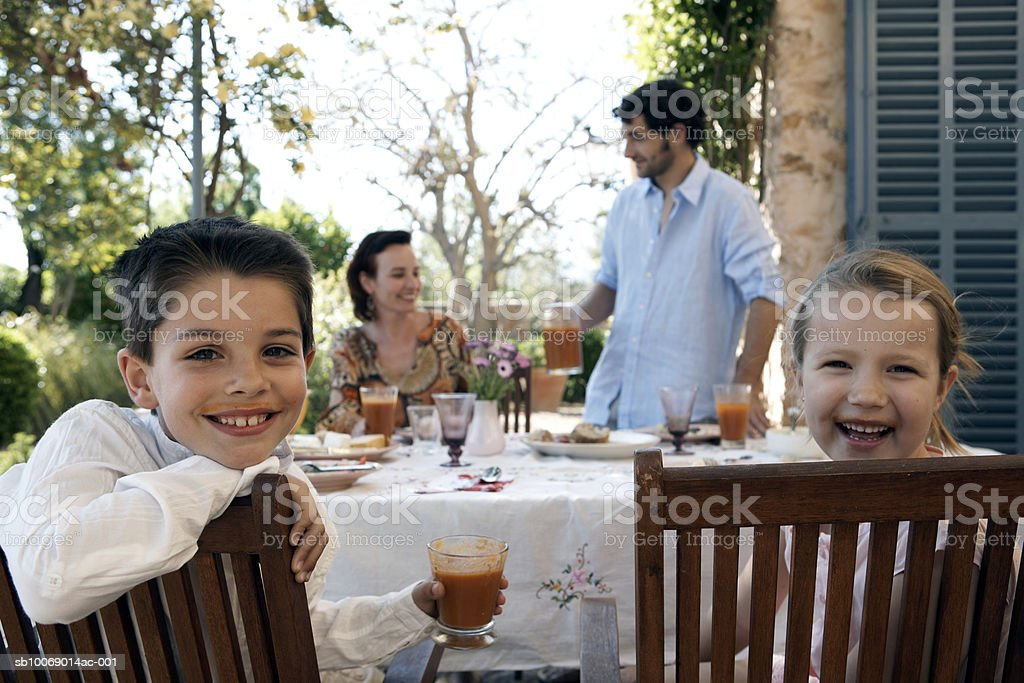 Family dining outdoors, children (8-9) looking at camera royalty-free stock photo