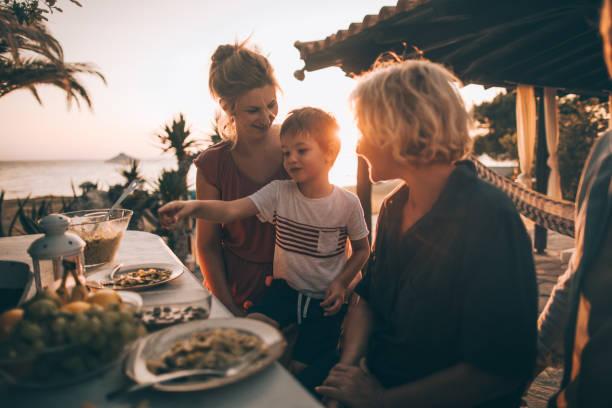 familienessen am meer - griechische partyspeisen stock-fotos und bilder
