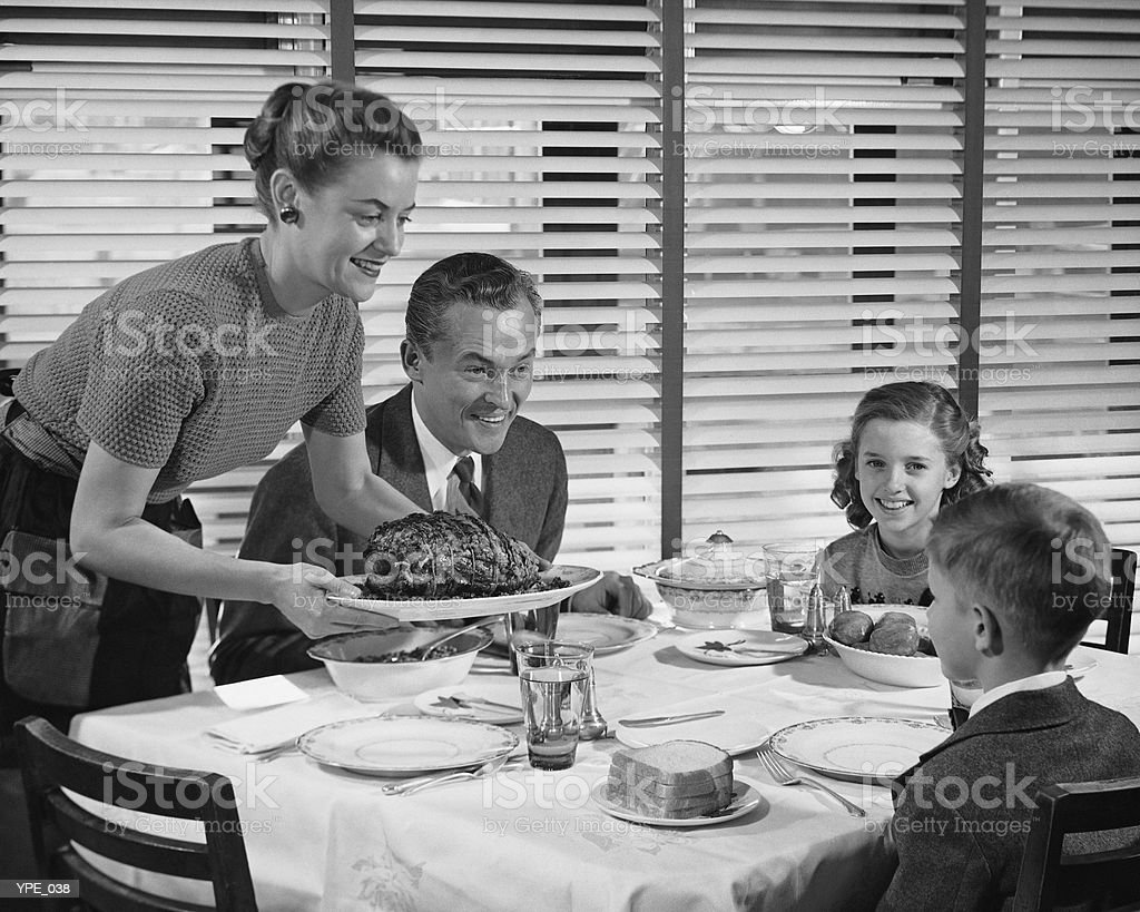 Family dinner, mother holding platter with roast on it royalty-free stock photo