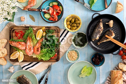 690274036 istock photo family dinner table with shrimp, fish grilled, salad, different snacks 686873522