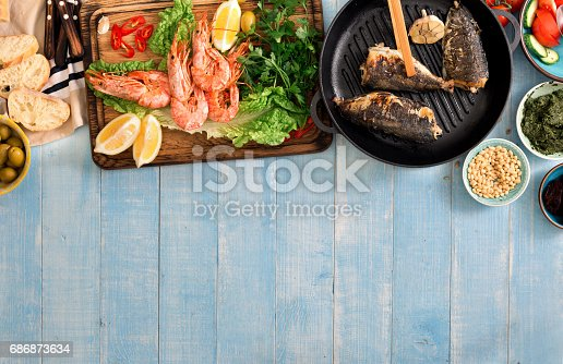 690274036 istock photo Family dinner table with shrimp, fish grilled, salad, different snacks with border 686873634