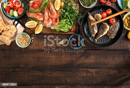 690274036 istock photo Family dinner table with shrimp, fish grilled, salad, different snacks with border 686873654