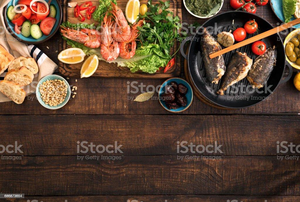 Familia mesa con camarón, pescado a la plancha, ensalada, aperitivos diferentes con la frontera - foto de stock