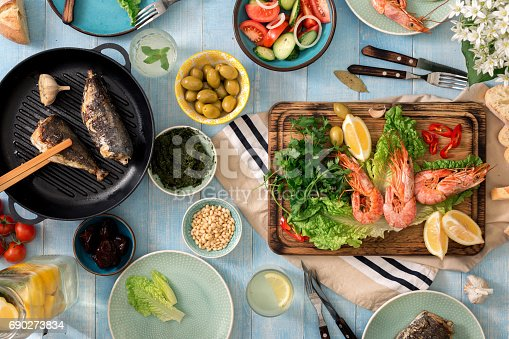690274036 istock photo Family dinner table with shrimp, fish grilled, salad, different snacks and homemade lemonade 690273834