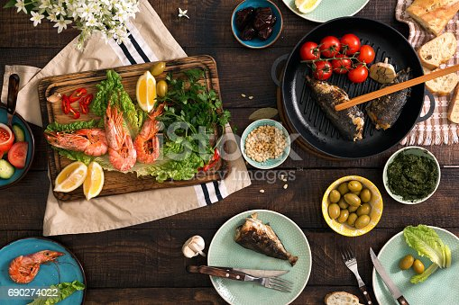 690274036 istock photo Family dinner table with shrimp, fish grilled, salad, different snacks 690274022
