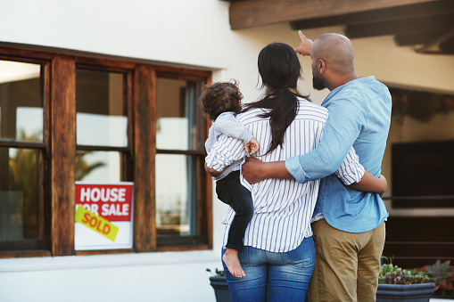 Shot of a young family of three facing their new home outside with a sold sign in the window file the father points towards the home