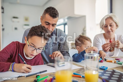 680535874 istock photo Family doing homework all together 1050961384