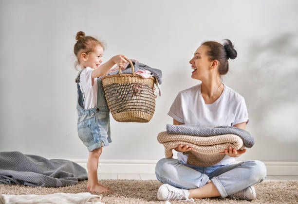 family doing laundry at home Beautiful young woman and child girl little helper are having fun and smiling while doing laundry at home. chores stock pictures, royalty-free photos & images