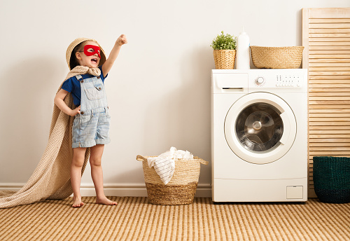 Beautiful child girl little helper is having fun and playing while doing laundry at home.
