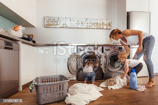 954356678istockphoto Family doing laundry together at home 1016529018
